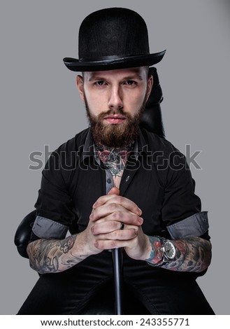 Serious gangster in hat sitting on leather chair holding cane