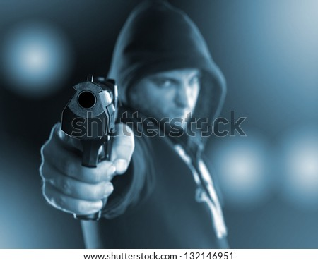 Serious gangster is aiming a gun to you. Toned in blue - stock photo