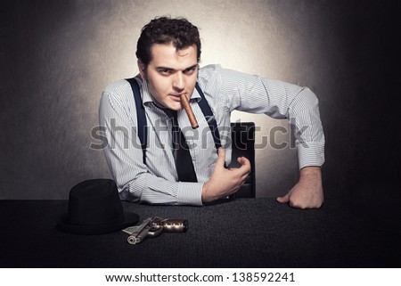 serious gangster sitting and looking at camera on grunge background - stock photo