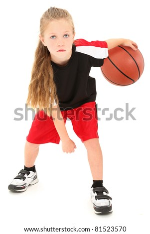 Serious girl child basketball player in uniform dribbling ball between legs over white background. - stock photo