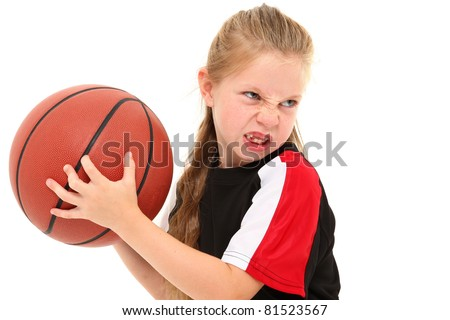 Serious girl child basketball player in uniform throwing ball between legs over white background. - stock photo