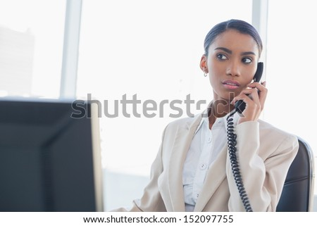 Serious gorgeous businesswoman on the phone in bright office - stock photo