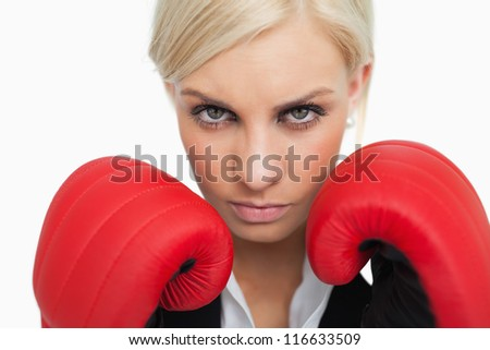 Serious green eyed woman with red gloves fighting against white background - stock photo
