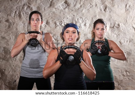 Serious group of three ladies lifting kettlebell weights - stock photo
