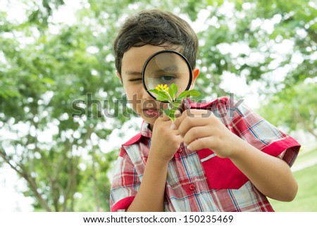 Serious guy exploring the environment with a magnifying glass - stock photo