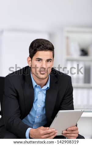 Serious handsome businessman holding a tablet computer in his hands leaning forwards looking at the camera with an earnest expression - stock photo