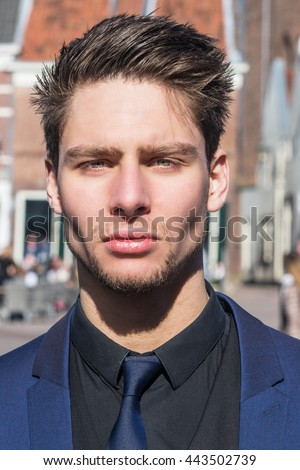 Serious handsome young man in European city. Attractive male model wearing a blue suit, black shirt and tie. - stock photo
