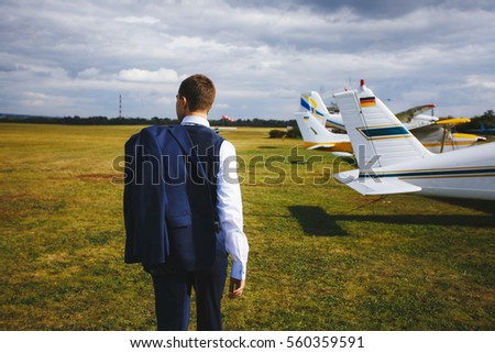 Serious handsome young man in the west and suit walk near small plane on the airfield