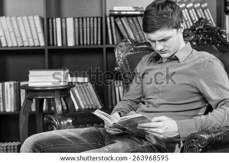 Serious Handsome Young Man Sitting on a Chair Near the Bookshelves While Reading a Book Seriously, Captured in Monochrome. - stock photo