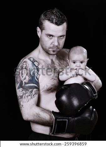 Serious hispanic boxer with a baby in her arms, on black background