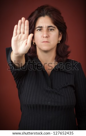 Serious hispanic woman with her hand extended signaling to stop (useful to campaign against violence or discrimination) - stock photo