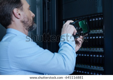 Serious IT administrator putting a rack server on its place