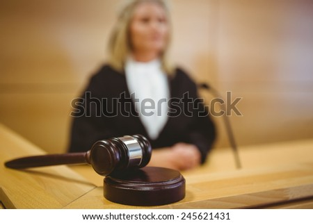 Serious judge with a gavel wearing robes in the court room - stock photo