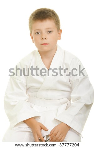 Serious karate kid sitting on knees against white background