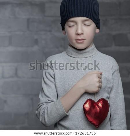 Serious kid holding heart, studio - stock photo