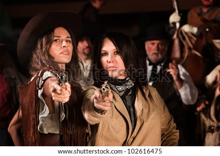 Serious ladies in western wear draw their revolvers - stock photo