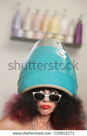 Serious lady looking over with head in hair dryer - stock photo