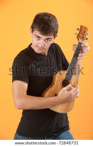 Serious Latino teen ukulele player on an orange background - stock photo