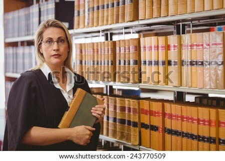 Serious lawyer holding a book in library - stock photo