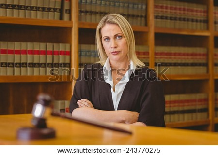 Serious lawyer looking at camera with arms crossed in library - stock photo