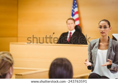 Serious lawyer make a closing statement in the court room - stock photo