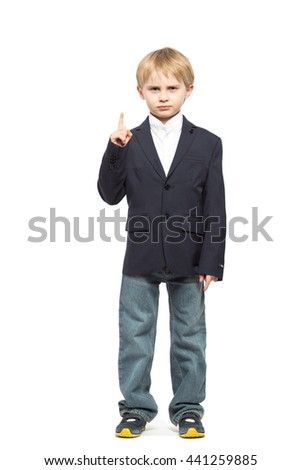 serious little boy blonde in a black jacket and jeans, raised his finger up and frowned. Isolated on white background. Shooting in the studio