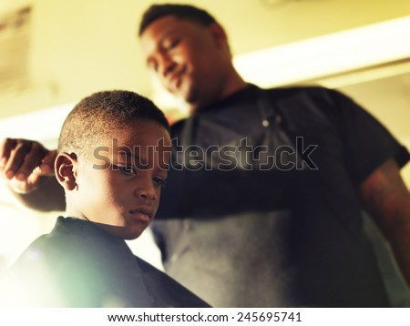 serious little boy in barber shop - stock photo