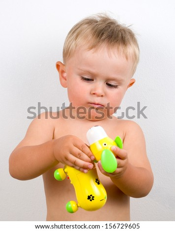 Serious little boy playing with plastic toy dog - stock photo