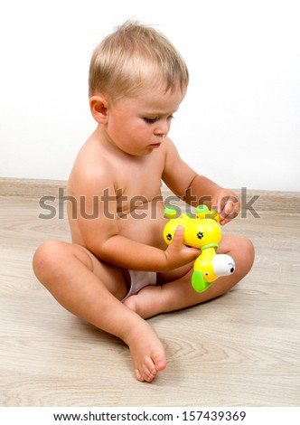 Serious little boy playing with plastic toy dog sitting on a floor - stock photo