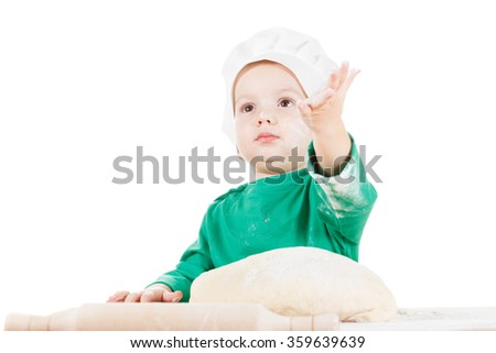 Serious little cook boy kneading the dough for the cookies, isolated on white background.  Half-length portrait of the table in studio