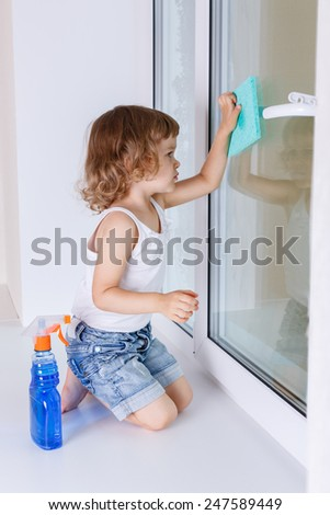 Serious little girl cleaning windows in the house. Mother's assistant. - stock photo