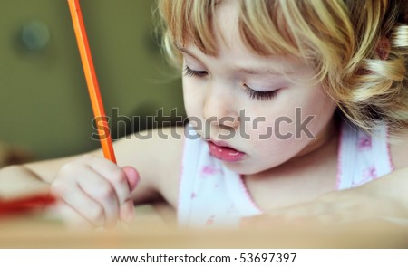 serious little girl drawing in soft selective focus - stock photo