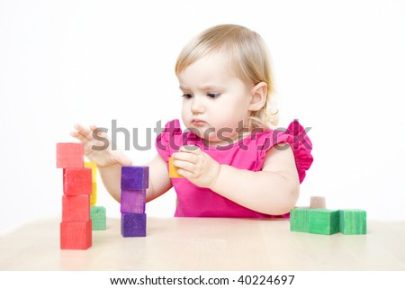 Serious little girl making towers from bricks