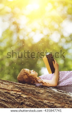 Serious little girl reading the Bible or a book on a big tree in the rays of sunset. - stock photo