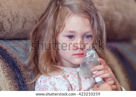 Serious little girl with cough using inhaler at home - stock photo