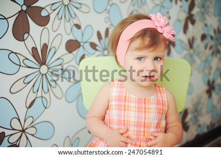 serious little girl with rose headband - stock photo