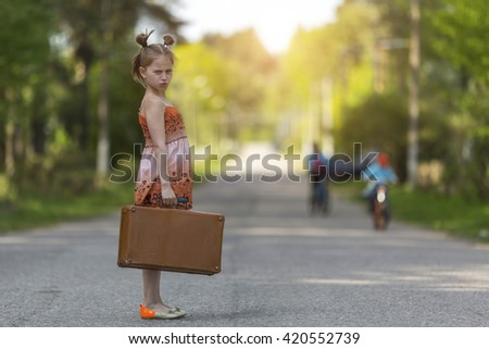 Serious little girl with suitcase standing on the road. - stock photo