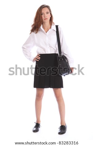 Serious look from young teenage secondary school student girl wearing black and white school uniform, with bag over her shoulder. - stock photo