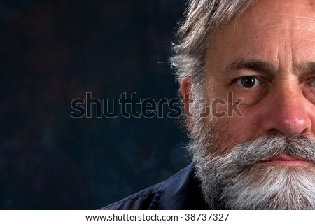 Serious look on a mature man's half face. Room for copy on left. - stock photo