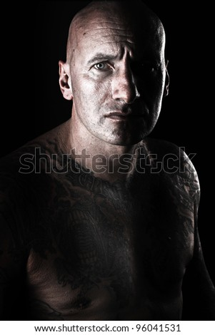 Serious looking bald man over black - stock photo