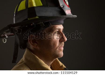 Serious looking confident firefighter Headshot Profile View Portrait on Dark Background - stock photo