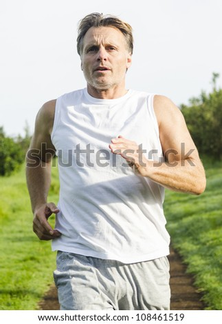 serious looking man running in park. - stock photo