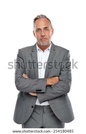 Serious looking mature businessman standing with his arms crossed against white background - stock photo