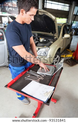 Serious looking mechanic working on a laptop in garage - stock photo