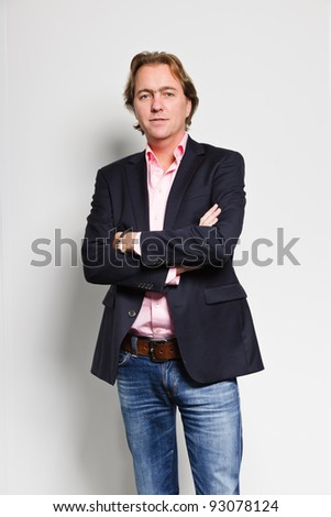 Serious looking young business man blond hair blue suit and pink shirt isolated on white background - stock photo