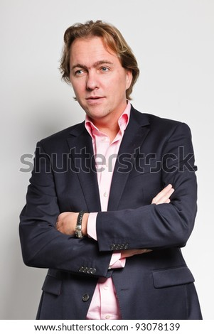 Serious looking young business man blond hair blue suit and pink shirt isolated on white background