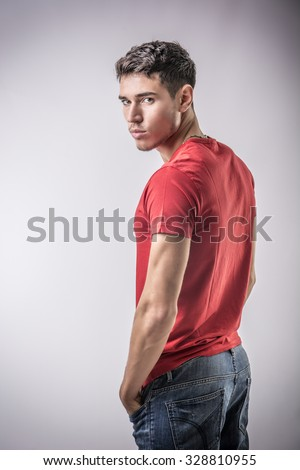 Serious looking young man wearing red t-shirt, turning around to look at camera on light background