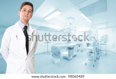 Serious male doctor with an operating room at the background - stock photo