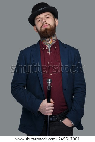 Serious male in blue costume and hat holding cane - stock photo