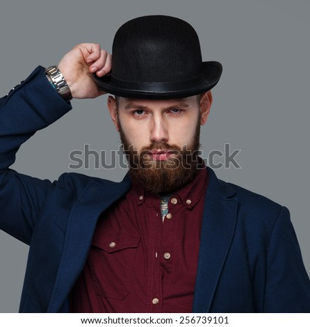 Serious male in blue costume and hat. Isolated on grey. - stock photo